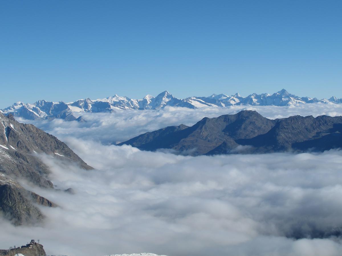 Saas Fee liegt unter einem Wolkenmeer. Im Hintergrund die Berner Alpen mit dem markanten Bietschhorn